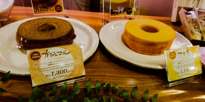 2011年創業のバウムクーヘン専門店「ふくぎや」。 比較的新しいお店ながら、沖縄の選りすぐりの食材である、黒糖や紅芋、蜂蜜、卵などををふんだんに使った贅沢なバウムクーヘンは、幸せを呼ぶバウムクーヘンとして、地元の方にも親しまれています。
