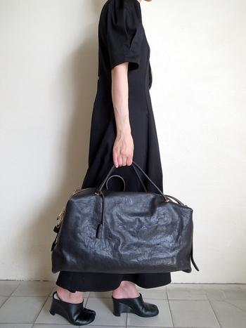 ボストンバッグをスタイリッシュに持つお手本のようなコーデ。ツヤのある美しい革のバッグなら、オールブラックでも重い印象になりません。