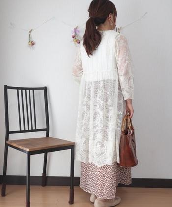 白いレースのガウンと、優しくて明るいカラーの花柄スカート。爽やかさの中に落ち着き感が漂っているのは、バッグの色味がこっくりカラーだから。でもクリア素材なので重たく見えません。