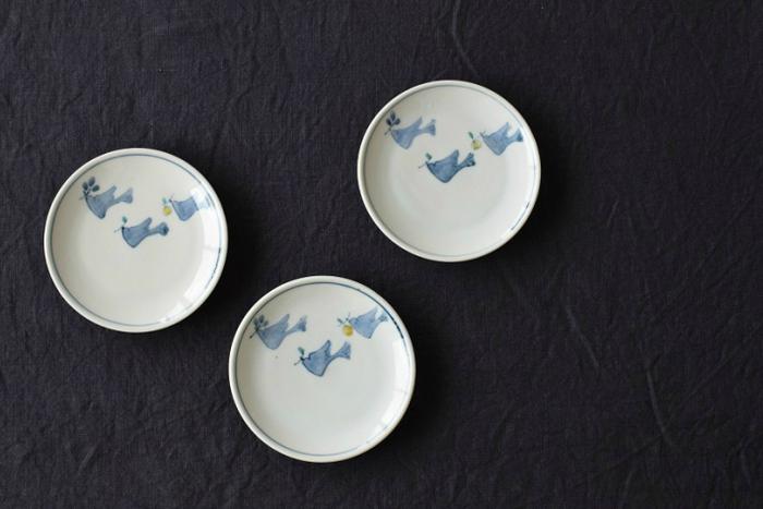 こちらは青い小鳥がお気に入りの木のみを見つけて飛び交う様子を描いた、シンプルで可愛い「色絵木の実集め」シリーズ。両手にすっぽりと収まる小ぶりの小皿は、3羽の小鳥をアクセントにした上品なデザインが印象的です。副菜やお菓子を盛る器としてはもちろんのこと、同じシリーズの蕎麦猪口のソーサーとしても使用できます。