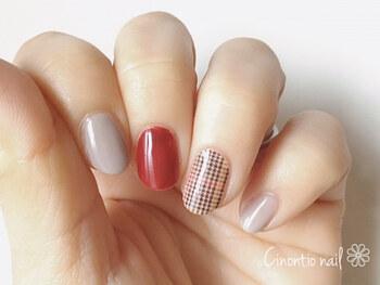 中指だけに赤を塗って。チェック柄のネイルシートの赤とリンクしているのがおしゃれですね。他の指で抜け感を出しているのも真似したいポイント。