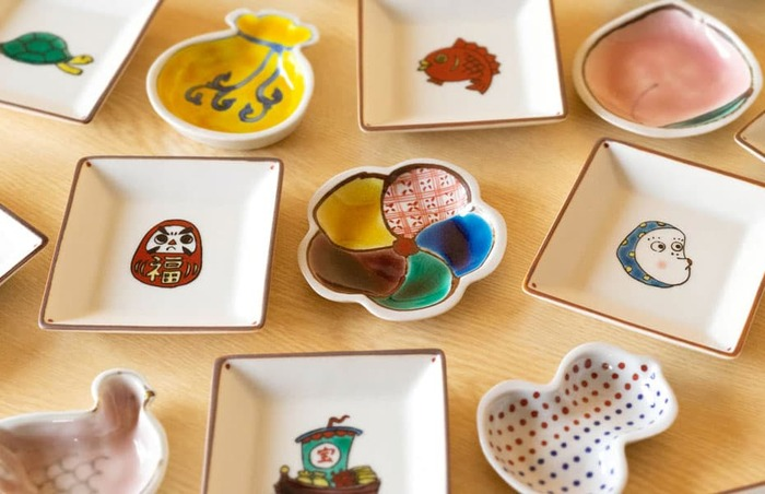 「九谷焼」とは石川県南部の金沢市・小松市・加賀市・能美市で生産されている陶磁器を指します。1650年代の江戸時代初期頃に誕生し、現在は「JAPAN KUTANI」として海外でも人気を集めている日本の伝統工芸品です。そんな九谷焼の魅力は何と言っても、色とりどりの五彩絵具や金で描いた華やかな色絵の美しさです。呉須(ごす)と呼ばれる渋い青色の顔料で図柄を描き、赤・黄・緑・青・紫の5色の絵具で彩色をほどこした華麗な絵付けが特徴です。