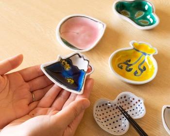 次にご紹介するのは、石川県・能美市にある九谷焼の窯元、「双鳩窯(そうきゅうがま)」の素敵な豆皿です。こちらは赤・黄・緑・青・紫の鮮やかな五彩の色絵をほどこした、華やかで可愛い「手のひら縁起」シリーズ。名前の通り手のひらにすっぽりと収まる小ぶりのサイズと、富士山やひょうたんなど縁起物をモチーフにしたおしゃれなデザインが特徴です。