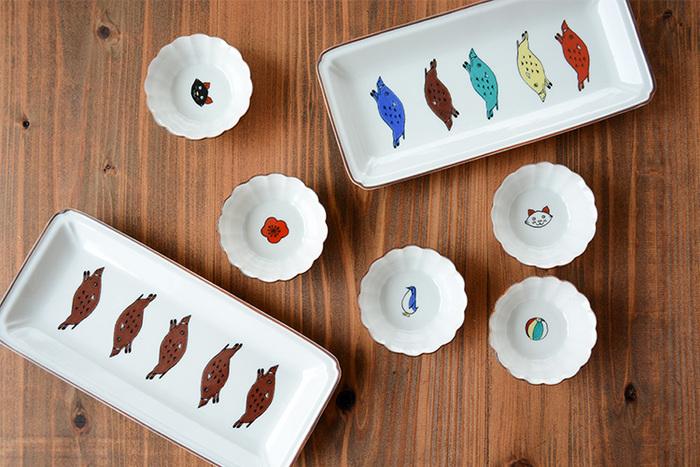 """九谷焼の老舗の窯元「上出長右衛門窯」と、日本独自の技術を活かした様々なプロダクトを提案する「丸若屋」が共に立ち上げた九谷焼のブランド「KUTANI SEAL(クタニシール)」。""""九谷焼をもっと身近に""""という思いから誕生した数々の器は、見ているだけで楽しくなるようなポップでユニークなデザインが特徴です。こちらは可愛いイノシシをモチーフにしたおしゃれな長皿と、愛らしい表情の猫やペンギンをデザインした菊小鉢。どちらも絵柄を印刷したシールを貼って器に焼き付けるという、九谷焼の転写技術を用いて作られています。"""