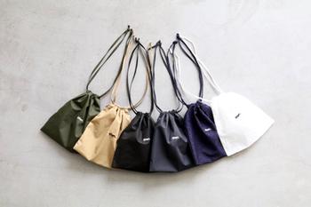 光沢のある生地で作られたコンパクトな巾着です。ベーシックな色居合で合わせるバッグやお洋服を選ばない。