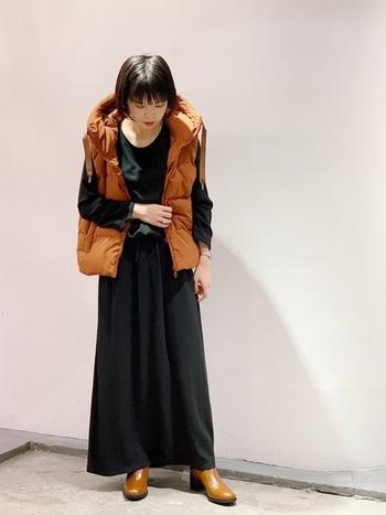 多くの色を使わないシンプルな大人コーデ。明るいオレンジベストでメリハリのある仕上がりに。身体を細く見せてくれる効果もあるブラックのワンピースなら、ボリューム感のあるダウンベストもバランス良く着こなせます。