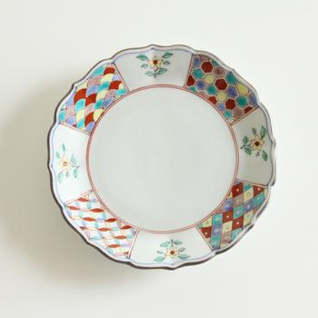 はじめにご紹介するのは石川県・小松市にある老舗の窯元、「宮本泰山堂(みやもとたいざんどう)」の美しい九谷焼の器です。こちらは花を模した輪花(りんか)形の器の縁に、古典的な図柄を描いた上品な絵皿です。