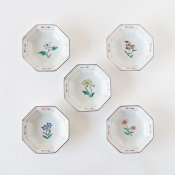 こちらの作品は、春から秋にかけて開花する「ひなげし・ドクダミ・くろゆり・なでしこ・キキョウ」の5種類の花を描いた八角花紋小皿です。細い絵筆で描かれた繊細な絵付けと、九谷焼ならではの華やかな色彩が印象的です。