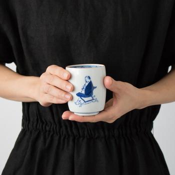 こちらは勢いよく走るイノシシに笛吹を座らせたユニークなデザイン。深い発色の藍色で描かれた笛吹の湯吞は、五彩の華やかな九谷焼とはまた一味違った、落ち着いた雰囲気が魅力的です。シンプルなデザインで和・洋どんな器にも合わせやすく、朝食・お茶の時間・晩ご飯と、一日の中の様々なシーンで活躍してくれます。