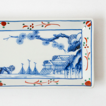 直径22㎝の小ぶりの長皿は、焼き魚や前菜を盛るのにちょうどいい大きさです。また、食事以外にも和菓子やフルーツを盛り付けたりと、幅広い用途に活躍してくれます。深い藍色で描かれた風景と、縁の部分の華やかな絵付けのコントラストも印象的です。なめらかな白い生地に、繊細なタッチで楼閣山水文を描いた美しい九谷焼は、インテリアとしてお部屋に飾るのも素敵ですよ。