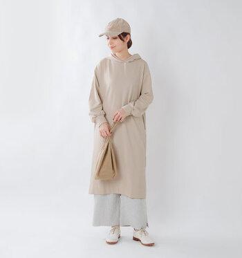ワイドスリーブとドロップショルダーで、トレンド感たっぷりな印象のベージュワンピース。フード付きのカジュアルな一枚を、ワイドパンツレイヤードとキャップでボーイッシュに着こなしています。全体を同系色でまとめているので、重ね着も重たく感じません。