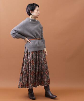 ハイネックとボリューム感のあるスリーブの組み合わせが、こなれ感たっぷりなグレーのプルオーバー。花柄のプリーツスカートを合わせて、レトロな着こなしに仕上げています。トップスはあえてタックインせず、ベルトのウエストマークでトレンド感もしっかりアピール。スカートと色味を合わせたショートブーツで、統一感をプラスしているのがポイントです。