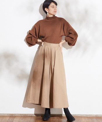 ハイネックのニットトップスは、袖にゆとりを持たせたワイドスリーブデザイン。ブラウンのトップスをベージュのフレアスカートにタックインして、季節感たっぷりな着こなしに仕上げています。足元は黒のショートブーツで、暖色を引き締める効果も◎