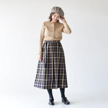 ベージュのベーシックなカーディガンを、チェック柄のフレアスカートにタックインした着こなしです。カーディガンはボタンをすべて留めてからタックインする、トップス風の着こなしがトレンド感抜群。チェック柄とベレー帽の組み合わせで、秋冬にぴったりのトラッドな雰囲気を演出しています。