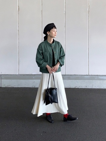 カーキのミリタリージャケットに、白のプリーツスカートを合わせた甘辛ミックスコーデ。ベレー帽・バッグ・シューズは黒で揃えて、足元の赤靴下がアクセントカラーとして活躍しています。