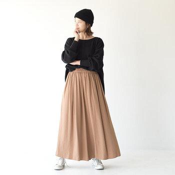 シンプルな黒のニット帽に、黒トップスとベージュのロングスカートを合わせたコーディネートです。オーバーサイズのトップスは、深めに被ったニット帽で顔周りをコンパクトにまとめてバランスよく着こなしています。
