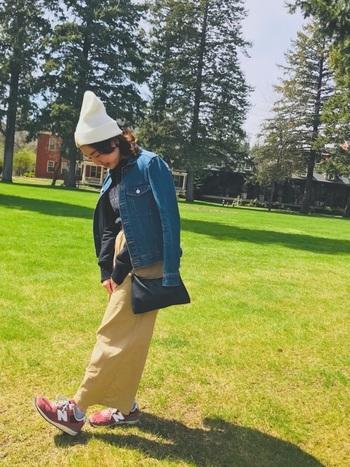 「Carhartt(カーハート)」の白ニット帽を、デニムジャケットとベージュのタイトスカートに合わせたカジュアルなコーディネート。インナーには黒のトップスを合わせて、ベーシックカラーの中に赤系スニーカーを差し色としてプラスしています。