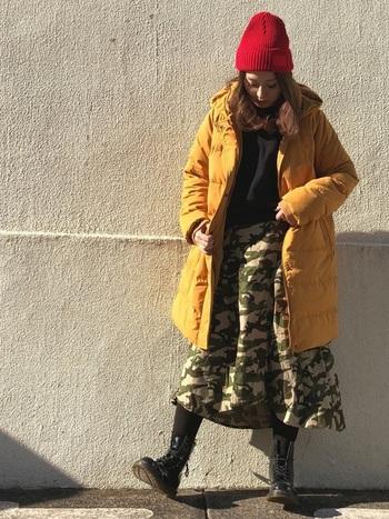 マスタードカラーのアウターに、迷彩柄のスカートが相性抜群なコーディネート。「NEW ERA(ニューエラ)」の赤ニット帽をプラスして、原色をアピールした明るめ元気コーデの完成です。足元は黒のショートブーツで、クールにまとめています。