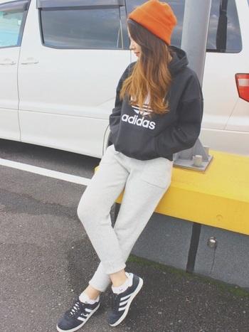 「adidas(アディダス)」の黒パーカーに、同ブランドで揃えたオレンジのニット帽が映えるラフなコーディネート。スウェットパンツとスニーカーでカジュアルに仕上げて、スポーツスタイルとしても活用できそうなスタイリングです。