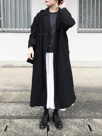 黒トレンチならモノトーンコーデも作りやすくて◎ふわりと軽さのある白のスカートをボトムスに持ってくれば、一気に垢抜けた印象に!