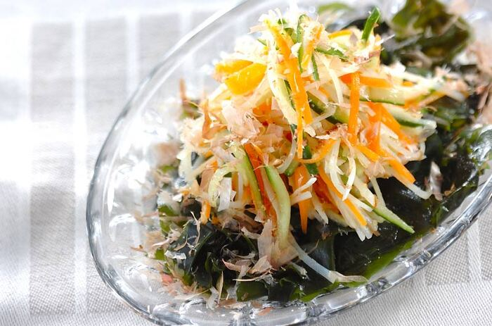 千切りにした野菜はさっと茹でることで、食べやすくドレッシングも馴染みやすくなります。たっぷりワカメを敷いて、ボリュームもアップ。