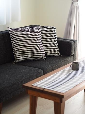濃い目のグレーのソファーには、白×黒の柄物のクッションを置いてスタイリッシュに。