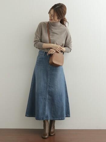 フレアーデザインがキレイなデニムロングスカート。ベージュのニットに、革のバッグ&ブーツで上品に着こなして。