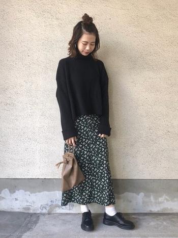 深いグリーン地に小花柄がちりばめられた、フェミニンなスカート。黒のニットを合わせてスタイリッシュに着こなして。