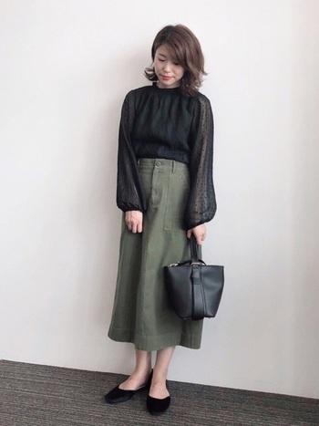 カジュアルな印象が強めのカーキのスカート。透け感あるエレガントなブラウスとかっちり目の革バッグを合わせてキレイに着こなします。