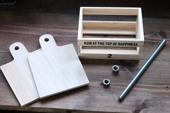 こちらは、セリアの100均アイテムでの作り方。  上でご紹介した「木製収納棚付き ペーパーホルダー」の作り方のように、カッティングボードの元々あいている穴を利用して作ります。  上では木の丸棒を使いましたが、こちらではこちらでは「ナガネジ」を使います。