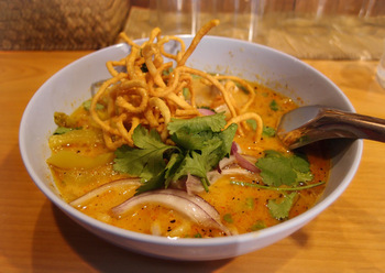 """もとは専門店だったこともあり、今でも人気の""""カオソーイ""""。ココナッツが効いた優しく深みのあるスープに、大きめにカットされた高菜がアクセント。"""