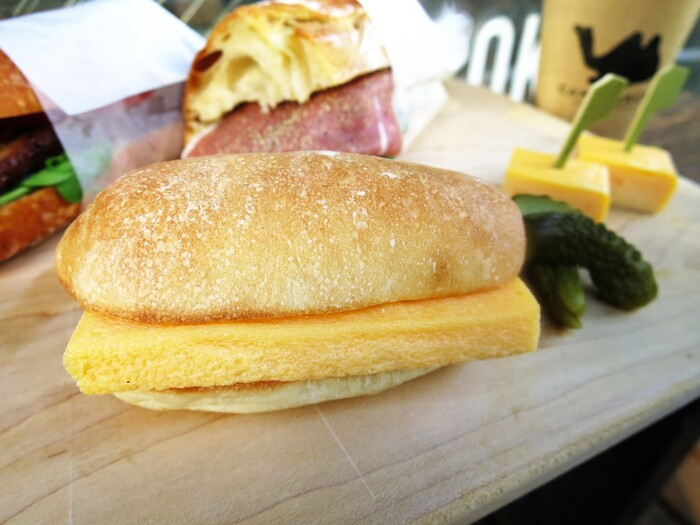 """玉子焼きに使う出汁は、鰹節より柔らかな風味を持つ鮪節から血合いを抜いた""""高級寿司店仕様""""。玉子焼きの甘やかさをパンに塗られた和辛子バターが引き締めてくれます。パンはカタネベーカリー製『もち麦コッペパン』。"""
