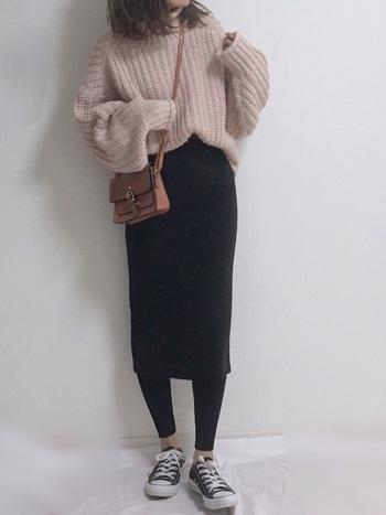 黒のタイトスカートは、ふんわりとしたピンクニットとの相性抜群!裾からレギンスを覗かせて、トレンド感をプラスしてみて。
