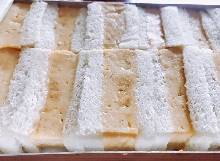 『玉子サンド』。耳をカットし、辛子マヨネーズを塗った食パンに関西風のだし巻き玉子をサンド。箱にきっちり詰められた姿が美しい。