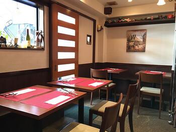 奥さんと旦那さんがふたりで経営している、雰囲気がある小さなレストラン。重厚なブラウンのテーブル、チェアに赤が映える可愛らしい店内です。