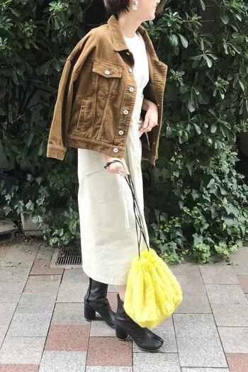 白トップス×タイトスカートを合わせたワントーンコーデに、ブラウンのコーデュロイジャケットを合わせた今っぽさ抜群のコーディネート。足元は黒のブーツでシンプルにまとめつつ、イエローのファーバッグをワンアクセントに活用しています。