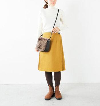 マスタードカラーの巻きスカートに、白トップスをタックインした暖かみのあるカラーリングのコーディネート。タイツやブーツ、バッグなどの小物はブラウン系で揃えて、イエローのスカートにしっかり馴染むよう計算された着こなしです。どんなアウターも合わせやすい、大人のベーシックコーデですね♪