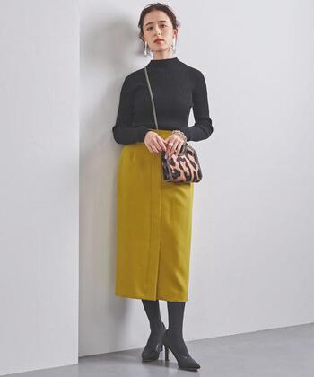 くすみイエローのタイトスカートに、黒のハイネックトップスをきっちりとタックインしたコーディネートです。タイツやパンプスもダークトーンでまとめて、色味のあるスカートを主役に。大ぶりなイヤーアクセサリーとレオパード柄のショルダーバッグで、女性らしさのアピールも忘れません。