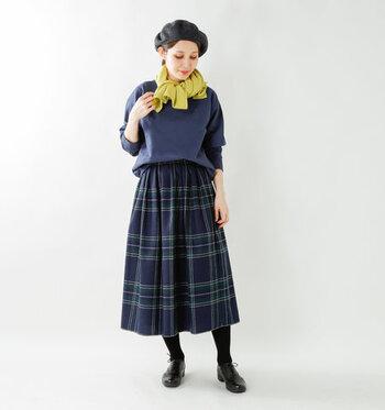 ネイビーのトップスに、同系色のチェック柄スカートを合わせたダークトーンコーデ。ベレー帽も色味を合わせて、全身を控えめカラーでシックにまとめています。そして、首元に巻いたイエローストールを差し色に。ストールはコンパクトに巻いても垂らしても、サマになります。
