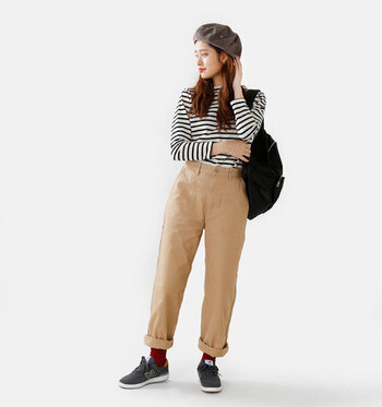 ベージュのワイドパンツに、黒のスニーカーを合わせて赤靴下を差し色アイテムに。パンツはロールアップして、赤靴下を見せる幅を調節。ボーダートップスや黒リュックなど、全体をシンプルなアイテムでまとめています。