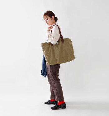 ブラウンのワイドパンツと、黒のローファーシューズの間に赤靴下を差し色としてプラス。控えめカラーのアイテムの中で、赤色の靴下は面積が狭くてもパッと目を引きますね。