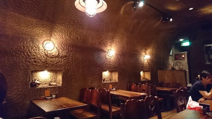 入り口の階段を下るとまるで絵本の世界に迷い込んだかのような異世界が。洞窟のような壁と天井ですが、店内は広々として席にもゆとりがあります。
