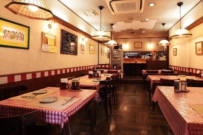 赤いギンガムチェックが可愛い店内。優しい木のぬくもりと、暖色のライトが居心地いい。1993年開業という愛され続ける、温かみのある内装です。
