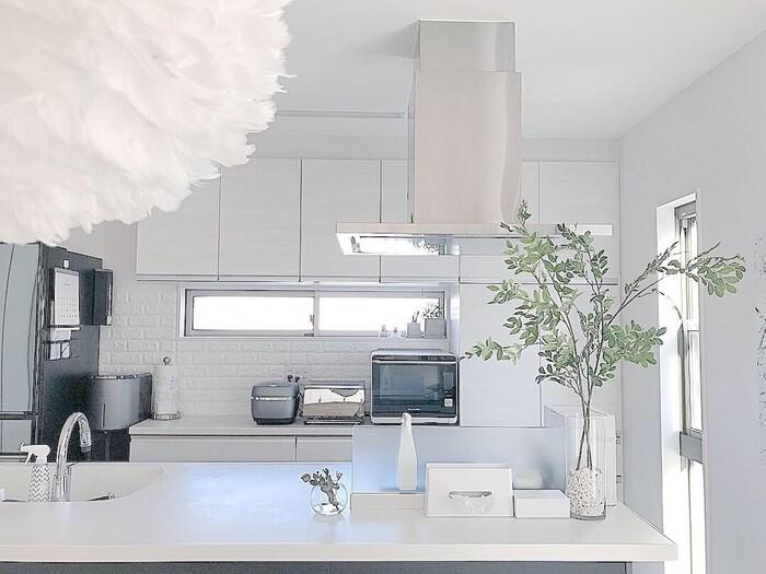白で統一されたキッチンカウンター。余計なモノは置かず、必要最低限のモノだけでインテリアをまとめています。グリーンを添えて、空間にみずみずしさを演出。透明感のあるガラス花器はスタイリッシュな白インテリアによく合います。
