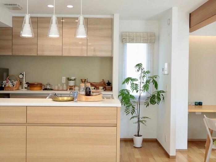 キッチンカウンターの上を照らすのは、吊り下げる収納のペンダントライト。同じデザインを3つ並べた多灯づかいが目を惹きます。調味料やキッチン雑貨も、インテリアの一部に。