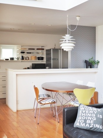白で統一されたキッチンカウンターは、アクセントクロスで個性をプラス。北欧雑貨とインテリアグリーンがアイキャッチになっています。
