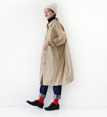 ベーシックなAラインのコートも、光沢感のあるデザインならカジュアルになりすぎません。デニムの裾から覗かせた赤のソックスがとってもおしゃれ!