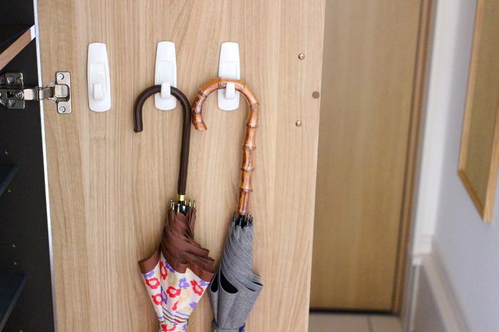 下駄箱の扉裏にフックをつけて、傘を掛ける収納に。 傘立てを置く必要がなく、玄関を広く使うことができます。