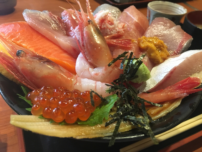 市場のあちこちで海鮮が溢れている近江町市場ですが、新鮮な魚介をお腹いっぱい食べたいという方は「じもの亭」がおすすめです。器から溢れるほどの厚切り魚介がまるで花咲くように盛られた「海鮮丼」はじもの亭の名物です。誰もが大満足の人気メニューです。