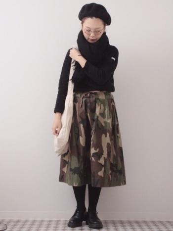 迷彩柄のミモレスカートは、ニットや足元を黒でまとめることで大人クールな雰囲気に。ベージュの大きめキャンバスショルダーで、縦ラインを強調しミリタリー感を和らげています。